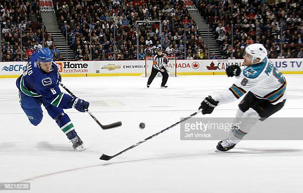 Joe Pavelski of the San Jose Sharks looks on as Sami Salo of the Vancouver Canucks takes a slapshot during the game at General Motors Place on March...