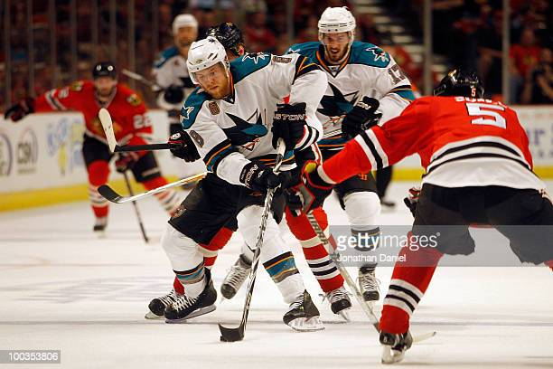 Joe Pavelski of the San Jose Sharks moves the puck against Brent Sopel of the Chicago Blackhawks in the first period in Game Four of the Western...