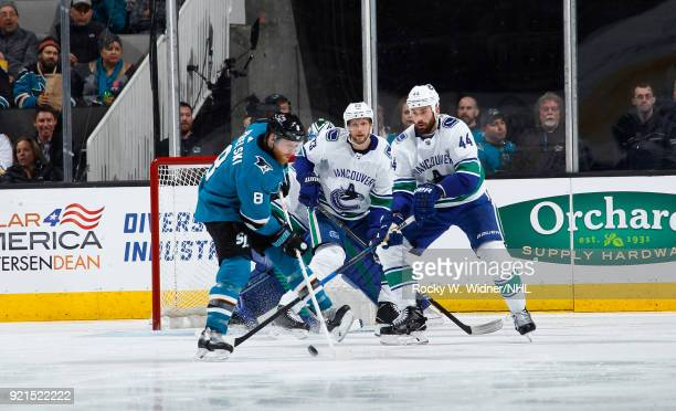 Joe Pavelski of the San Jose Sharks skates with the puck against Alexander Edler and Erik Gudbranson of the Vancouver Canucks at SAP Center on...