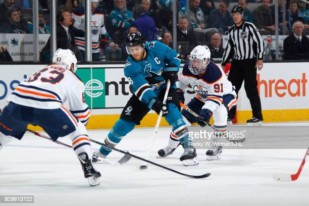 Joe Pavelski of the San Jose Sharks skates with the puck against Matthew Benning and Drake Caggiula of the Edmonton Oilers at SAP Center on February...