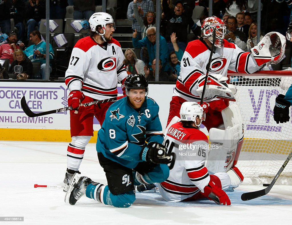 Joe Pavelski #8 of the San Jose Sharks smiles after scoring his goal against Justin Faulk #27, Ron Hainsey #65, and Eddie Lack of the Carolina Hurricanes during a NHL game at the SAP Center at San Jose on October 24, 2015 in San Jose, California.