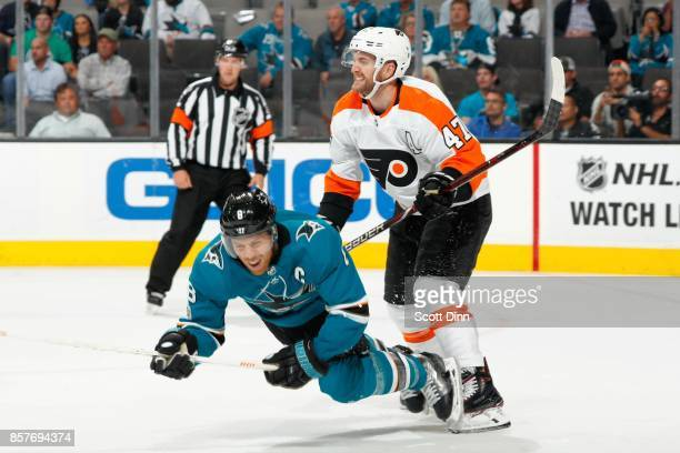 Joe Pavelski of the San Jose Sharks takes a hard check from Andrew MacDonald of the Philadelphia Flyers during a NHL game at SAP Center at San Jose...