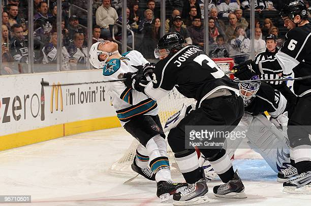 Joe Pavelski of the San Jose Sharks takes a hit from Jack Johnson of the Los Angeles Kings during the game on January 11, 2010 at Staples Center in...
