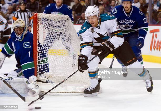 Joe Pavelski of the San Jose Sharks tries to get a handle of the puck while attempting a wrap around on goalie Roberto Luongo of the Vancouver...