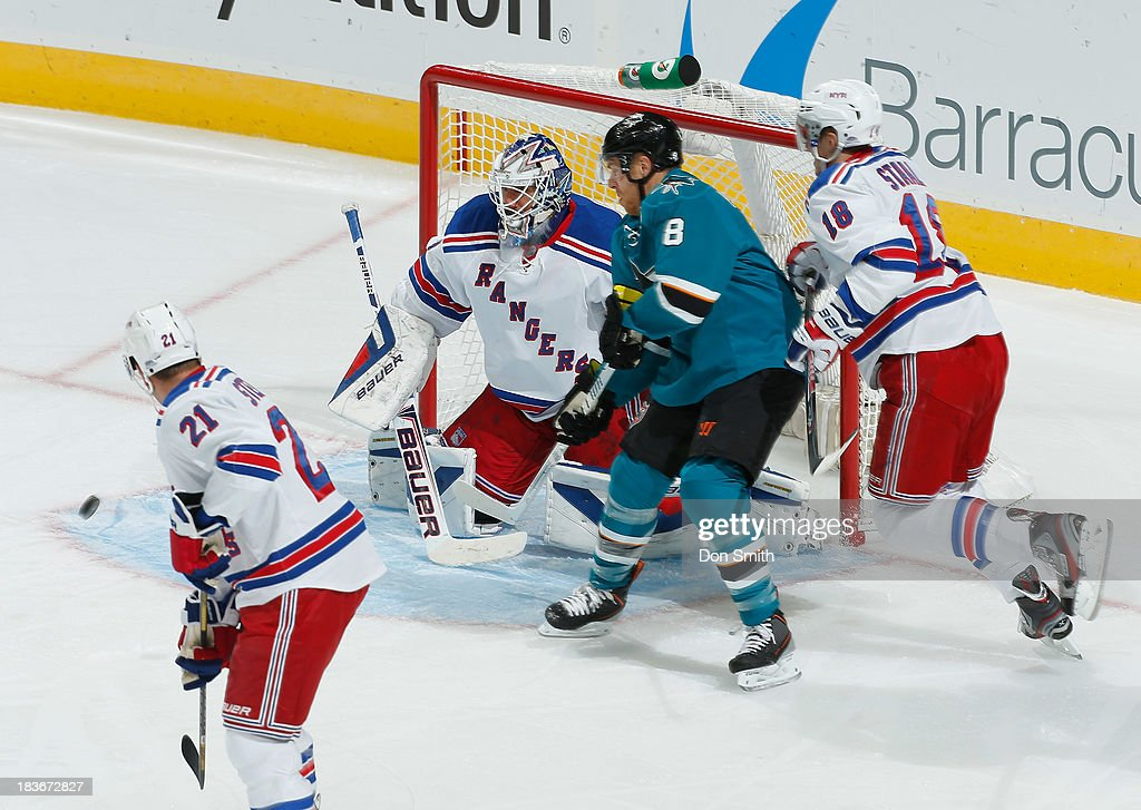 Joe Pavelski #8 of the San Jose Sharks watches as Marc-Edouard Vlasic's shot goes in the net against Henrik Lundqvist #30, Marc Staal #18 and Derek Stepan #21 of the New York Rangers during an NHL game on October 8, 2013 at SAP Center in San Jose, California.