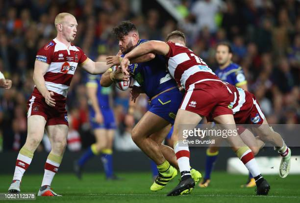 Joe Philbin of the Warrington Wolves is tackled by Sam Powell and Ryan Sutton of the Wigan Warriors during the BetFred Super League Grand Final...
