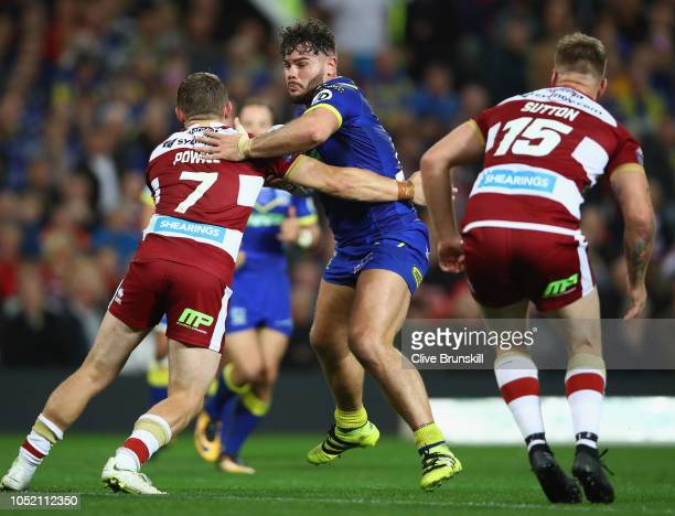 Joe Philbin of the Warrington Wolves is tackled by Sam Powell of the Wigan Warriors during the BetFred Super League Grand Final between Warrington...