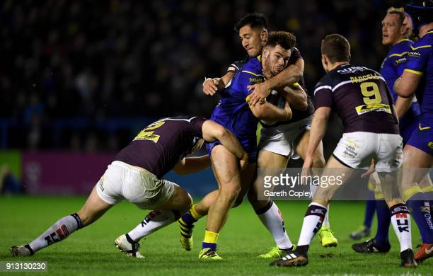 Joe Philbin of Warrington is tackled by Brad Singleton of Leeds during the Betfred Super League match between Warrington Wolves and Leeds Rhinos on...
