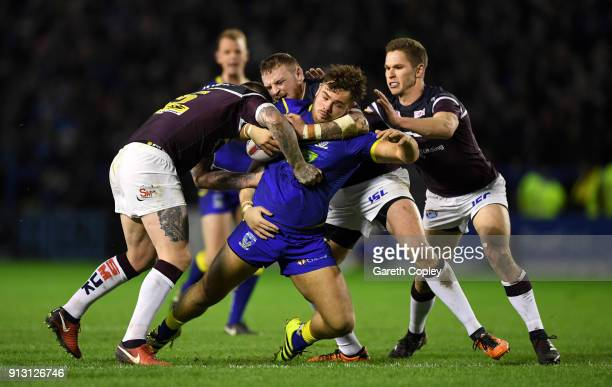 Joe Philbin of Warrington is tackled by Brett Delaney Brad Singleton and Matt Parcell of Leeds during the Betfred Super League match between...