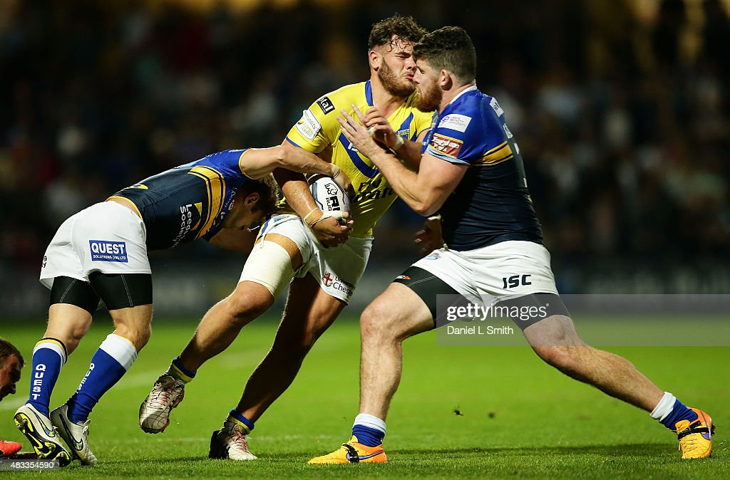 Joe Philbin of Warrington Wolves is tackled by Mitch Garbutt and Rob Burrow of Leeds Rhinos during the Round 1 match of the First Utility Super League Super 8s between Leeds Rhinos and Warrington Wolves at Headingley Carnegie Stadium on August 7, 2015 in Leeds, England.