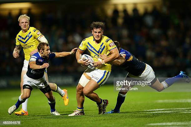Joe Philbin of Warrington Wolves is tackled by Mitch Garbutt of Leeds Rhinos during the Round 1 match of the First Utility Super League Super 8s...
