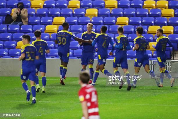 Joe Pigott of AFC Wimbledon celebrates with his team mates after scoring his teams first goal during the Sky Bet League One match between AFC...