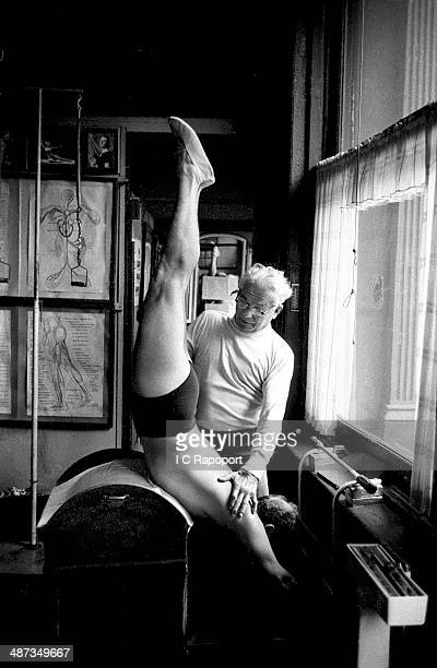 Joe Pilates Inventor physical fitness guru and founder of the Pilates exercise method instructs a client on the barrel and works him through an...