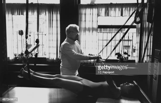 Joe Pilates Inventor physical fitness guru and founder of the Pilates exercise method instructs a client on the Cadillac and works her through an...