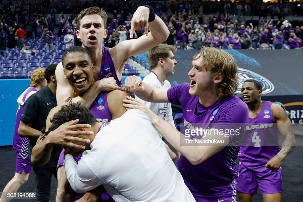 Joe Pleasant of the Abilene Christian Wildcats is surrounded by teammates after his winning free throw to defeat Texas Longhorns 53-52 in the first...