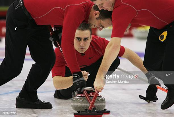 Joe Polo of United States releases a stone as Shawn Rojeski and John Shuster of United States brush the ice during the Gold medal match of the men's...