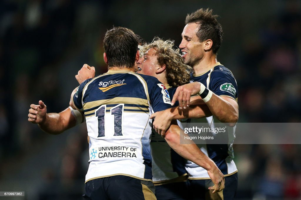 Joe Powell (C) of the Brumbies celebrates his try with teammates James Dargaville (L) and Andrew Smith during the round nine Super Rugby match between the Hurricanes and the Brumbies at McLean Park on April 21, 2017 in Napier, New Zealand.