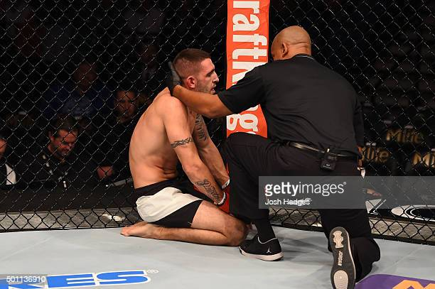 Joe Proctor is inspected by a referee after being defeated by Magomed Mustafaev of Russia in their lightweight bout during the UFC 194 event inside...