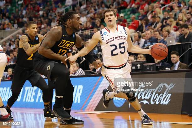 Joe Rahon of the St Mary's Gaels is defended by Mo AlieCox of the Virginia Commonwealth Rams during the first round of the 2017 NCAA Men's Basketball...