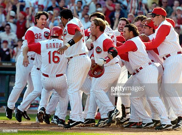 Joe Randa of the Cincinnati Reds is mobbed by teammates at home plate after hitting the game winning home run against the New York Mets in the bottom...