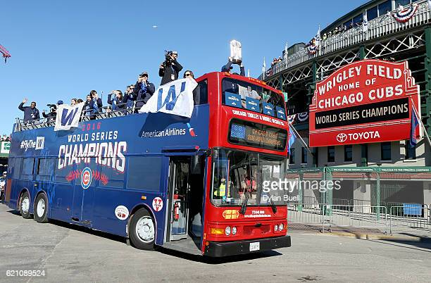 Joe Ricketts hoists the World Series trophy atop a bus driving past Wrigley Field during the 2016 World Series victory parade for the Chicago Cubs on...
