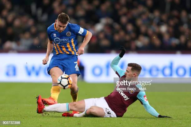 Joe Riley of Shrewsbury Town is challenged by Antonio Martinez of West Ham United during the Emirates FA Cup Third Round Repaly match between West...