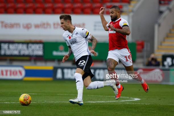 Joe Rodon of Swansea City is chased by Kyle Vassell of Rotherham United during the Sky Bet Championship match between Rotherham United and Swansea...