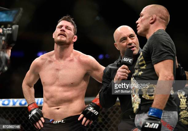 Joe Rogan interviews Georges StPierre of Canada as Michael Bisping of England looks on aftertheir UFC middleweight championship bout during the UFC...