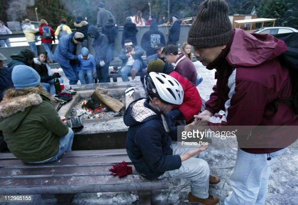 Joe Rong right warms the hands of his son Daniel Rong center as they take a break alongside the campfire at the Yosemite Outdoor Ice Rink in Yosemite...