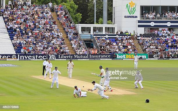 Joe Root and Alastair Cook look on as Adam Lyth catches the ball to dismiss Mitchell Starc of Australia during day four of the 1st Investec Ashes...