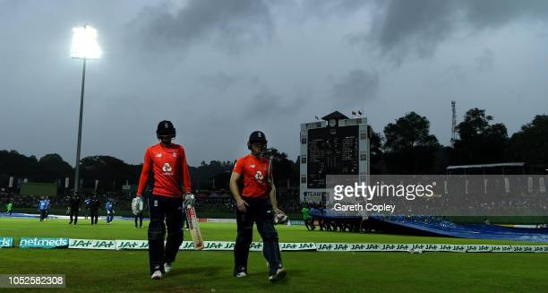 Joe Root and Eoin Morgan of England leave the field as rain stops play during the 4th One Day International match between Sri Lanka and England at...