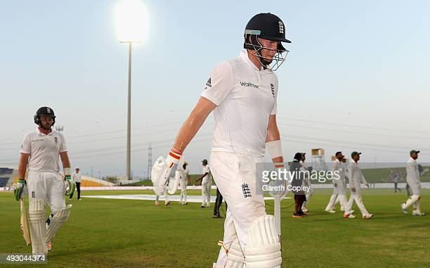 Joe Root and Ian Bell of England leave the field after bad light stops play on day five of the 1st Test between Pakistan and England at Zayed Cricket...