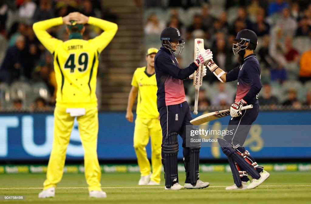 Joe Root and Moeen Ali of England celebrate as they hit the winning runs as Australian captain Steven Smith looks on during game one of the One Day International Series between Australia and England at Melbourne Cricket Ground on January 14, 2018 in Melbourne, Australia.