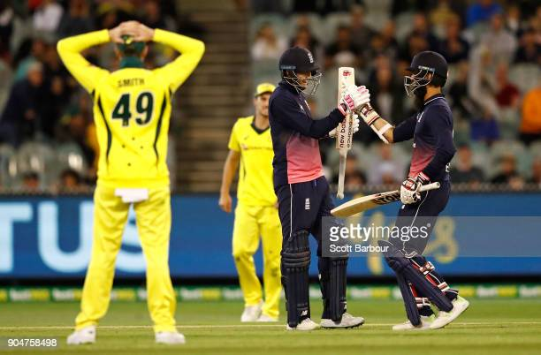 Joe Root and Moeen Ali of England celebrate as they hit the winning runs as Australian captain Steven Smith looks on during game one of the One Day...