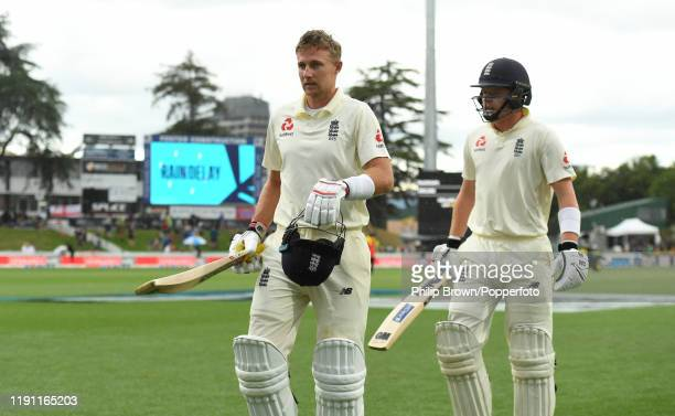 Joe Root and Ollie Pope leave the field as the rain falls during day 3 of the second Test match between New Zealand and England at Seddon Park on...