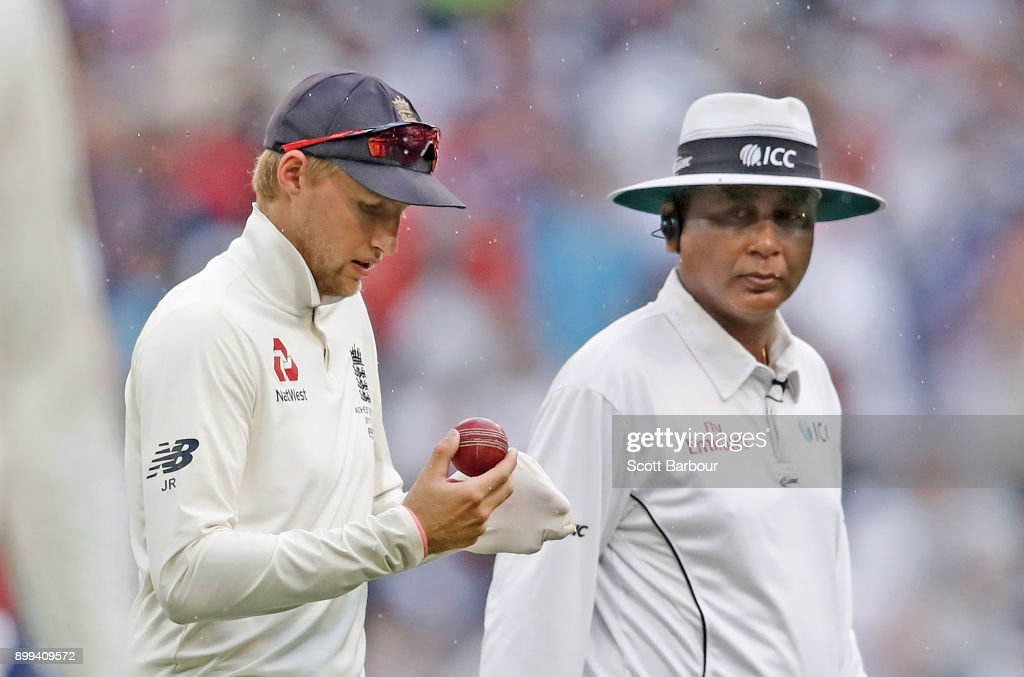 Joe Root, captain of England shines the ball as umpire Sundaram Ravi watches him during day four of the Fourth Test Match in the 2017/18 Ashes series between Australia and England at Melbourne Cricket Ground on December 29, 2017 in Melbourne, Australia.