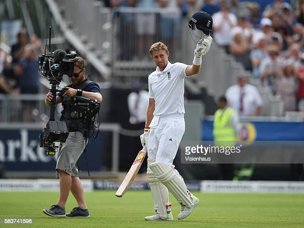 Joe Root of England acknowledges the fans as he is followed off the pitch by a Sky Sports television cameraman at the end of his innings during day...