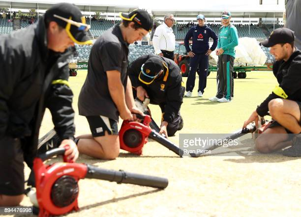 Joe Root of England and Steve Smith of Australia peak with Umpire Marais Erasmus as groundsmen dry the pitch after rain delayed the start of play...