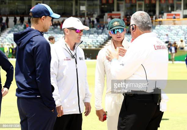 Joe Root of England and Steve Smith of Australia speak with the umpires as groundsmen dry the pitch after rain delayed the start of play during day...