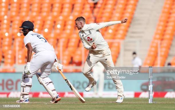 Joe Root of England bowls watched on by Washington Sundar of India during Day Two of the 4th Test Match between India and England at Sardar Patel...