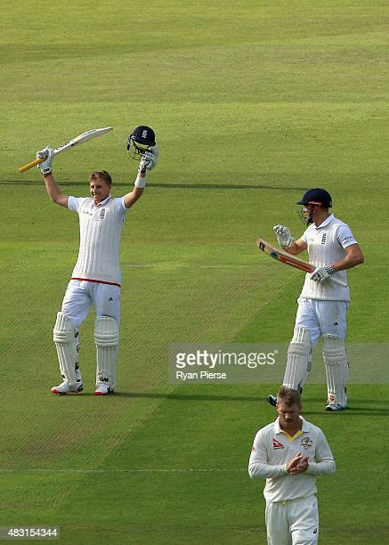 Joe Root of England celebrates after reaching his century and is applauded by Jonny Bairstow of England and David Warner of Australia during day one...