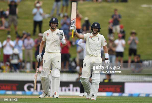 Joe Root of England celebrates after reaching his century near Zac Crawley during day 3 of the second Test match between New Zealand and England at...