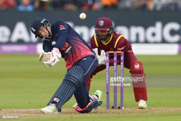 Joe Root of England hits a six off the bowling of Ashley Nurse as wicketkeeper Shai Hope of West Indies looks on during the third Royal London One...