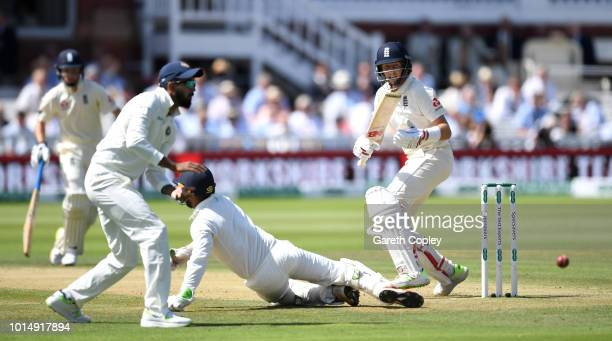 Joe Root of England hits past India wicketkeeper Dinesh Karthik and Ajinkya Rahane during day three of the 2nd Specsavers Test between England and...