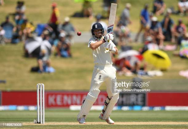 Joe Root of England hits the ball in the air and is caught during day five of the first Test match between New Zealand and England at Bay Oval on...