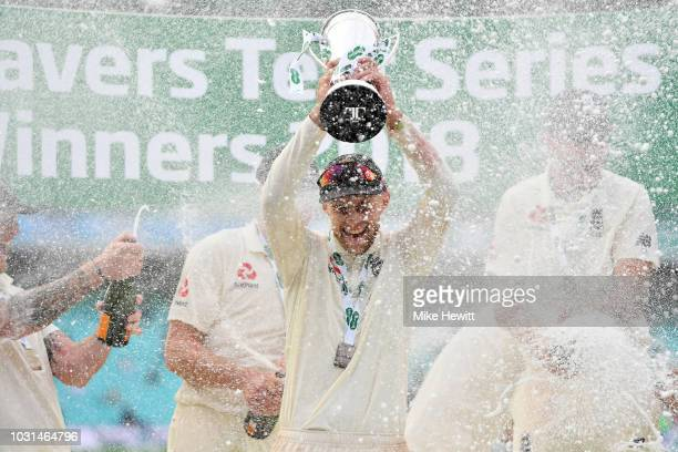 Joe Root of England is covered in champagne as he holds aloft the Winner's Trophy during the Specsavers 5th Test Day Five between England and India...