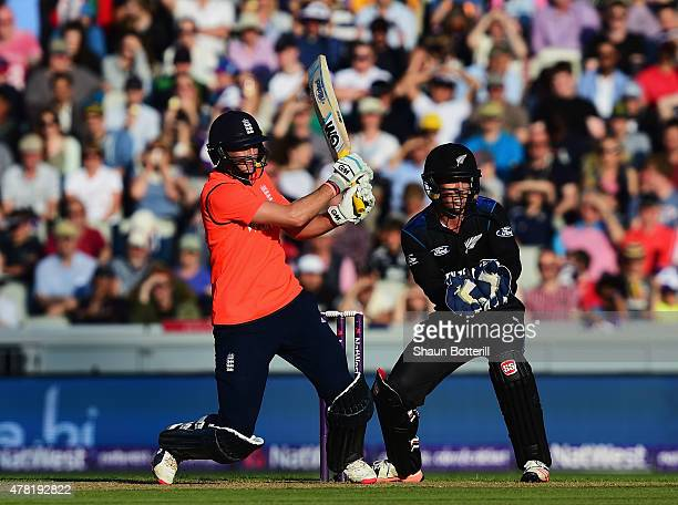 Joe Root of England plays a shot as Luke Ronchi of New Zealand looks on during the NatWest International Twenty20 match between England and New...