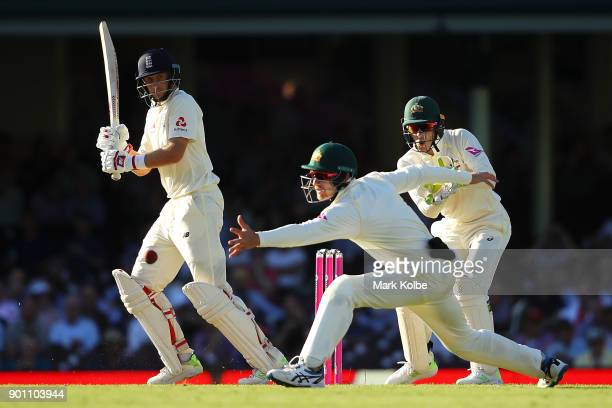 Joe Root of England plays the ball past Cameron Bancroft of Australia as Tim Paine of Australia watches on during day one of the Fifth Test match in...