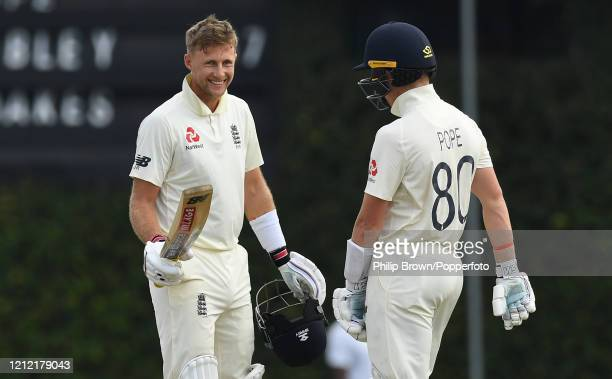 Joe Root of England reaches his century watched by Ollie Pope during the second day of the match between a Sri Lanka Board President's XI and England...