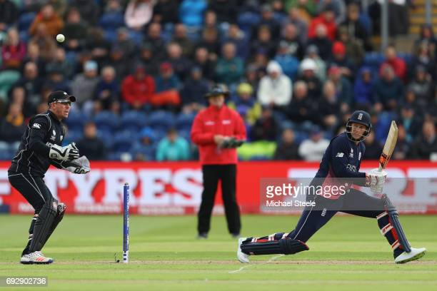Joe Root of England reverse sweeps a delivery as wicketkeeper Luke Ronchi looks on during the ICC Champions Trophy match between England and New...
